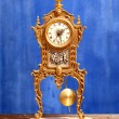 Ancient vintage golden brass pendulum clock - Stock Photo