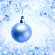 Christmas silver bauble on blue winter ice — Stock Photo