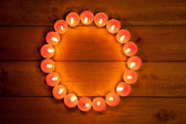 Candles cirlce shape on warm golden wood — Stock Photo