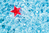 Christmas red glass star on cold blue ice — Stock Photo