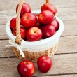 Basket of red apples on wood floor — Stock Photo