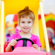 Blond children girl driving toy car - Stok fotoğraf