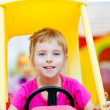 Blond children girl driving toy car - Stock Photo