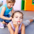 Beautiful little little girls lying on playground floor — Stock Photo