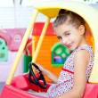 Children girl driving a toy car - Stock Photo