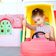 Children girl driving a toy car with ok gesture - Stock Photo