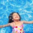 Royalty-Free Stock Photo: Brunette children girl swimming blue tiles pool