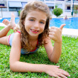 Children girl lying on pool grass in summer - Stock Photo
