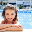 Happy kid girl smiling at swimming pool - Stock Photo