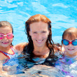 Daughters and mother family swimming in pool — Stock Photo #7109767