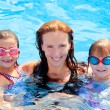 Daughters and mother family swimming in pool - Stock Photo