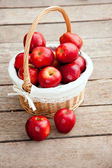 Basket of red apples on wood floor — Stok fotoğraf