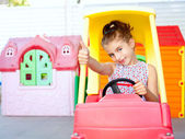 Children girl driving a toy car with ok gesture — Stock Photo