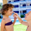 Mother puts sunscreen cream to daughter - Stock Photo