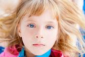 Beautiful blond blue eyes girl lying — Stock Photo