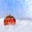 Christmas bauble on white fur and lights — Stock Photo