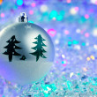 Christmas silver bauble on colorful glowing ice — Stock Photo