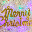 Merry christmas written in gold over ice - Stock Photo