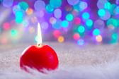 Christmas red candle on fur and colorful light — Stock Photo