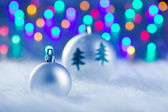 Christmas silver baubles witn tree and lights — Stock Photo