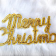 Merry christmas written in gold on white fur - Stock Photo