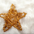 Christmas golden star over white fur - Stockfoto