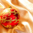 Stock Photo: Christmas red bauble on golden fabric