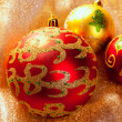 Christmas red baubles on golden fabric — Stock Photo