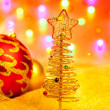 Christmas golden tree with baubles and lights - Stock Photo