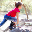 Hiking little girl climbing a rock in forest — Foto Stock