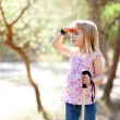 Hiking kid girl searching hand in head in forest - Foto de Stock  