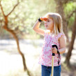 Hiking kid girl searching hand in head in forest - Foto Stock