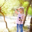 Hiking kid girl searching hand in head in forest - Stock fotografie
