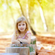 Blond kid girl in tree trunk forest — Stock Photo #7232413