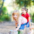 Kid girls playing on trunks in forest nature — Stock Photo #7232579