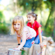 Kid girls playing on trunks in forest nature — Stock Photo #7232601