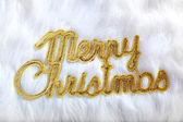 Merry christmas written in gold on white fur — Stock Photo