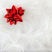 Christmas red ribbon look over white fur — Stock Photo