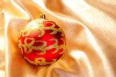 Adorno de Navidad rojo en tela dorada — Foto de Stock