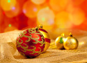 Christmas golden and red baubles in blur lights — Stock Photo