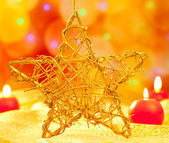 Christmas golden star candles in blurred lights — Stock Photo