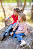 Friends kid girls playing in forest rock — Stock Photo