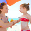 Daughter and mother in beach with sunscreen - Stock Photo