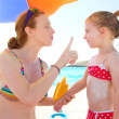 Daughter and mother in beach with sunscreen — Stock Photo