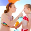 Stock Photo: Daughter and mother in beach with sunscreen