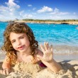 Little girl greeting hand gesture in sandy beach - Stock Photo