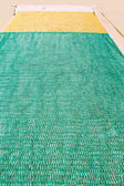 Green and yellow fishing net on the floor — Stock Photo