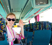 Girl on tourist bus happy with sunglasses — Stock Photo