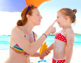 Daughter and mother in beach with sunscreen — Stok fotoğraf