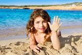 Little girl greeting hand gesture in sandy beach — Stockfoto